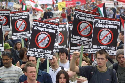 May 2002: Demonstrators in Berlin with signs reading 'No Attack Against Iraq - Warmongers Not Welcome' with a portrait of U.S. President George W. Bush.