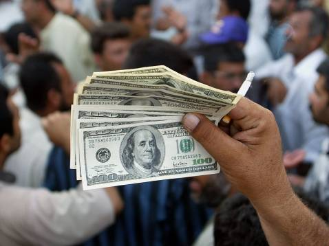 A Basra vendor holds up a stack of US 100 dollar bills as he exchanges money at the Al-Khadara Market in the heart of the southern Iraqi port city 22 May 2003.