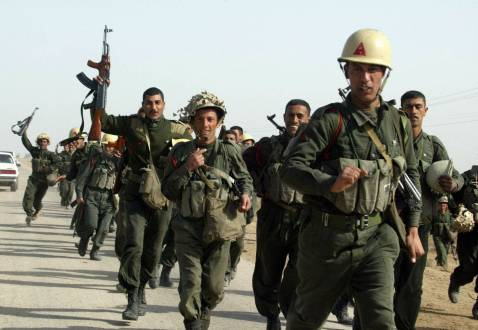 Iraqi Republican Guard troops run during a physical enduring exercise outside the al-Aziziya military facility, some 100 kms southeast of Baghdad, 06 March 2003.