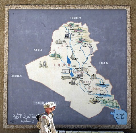 BABYLON, IRAQ: Two US coalition soldiers walk in front of a map of Iraq hung on the museum wall at ancient city of Babylon south of Bagdad.