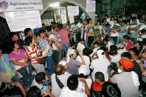 MANILA, PHILIPPINES: Filipinos applying for work in Iraq crowd outside a Manila recruitment agency.