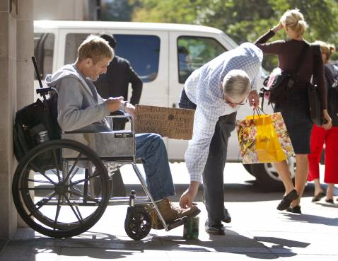 CHICAGO - SEPTEMBER 30: A passerby drops some loose change into the can of a homeless, disabled veteran in his wheelchair looking for money along the shopping area known as the 'Magnificent Mile' on Michigan Ave.
