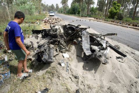 Iraqi boy inspects remains of a car bomb, Suleikh, Baghdad, June 2005.