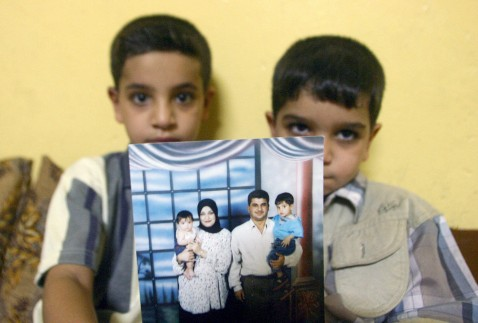 BASRA, Iraq: Hassan (L) sits with his younger brother Ali as they show off a family photo at their home in Basra, 500 kms south of Baghdad 20 July 2005. British Corporal Donald Payne, 34, faces manslaughter charges over the death of their father.
