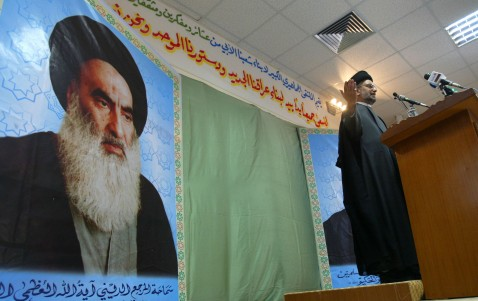 BAGHDAD, IRAQ - SEPTEMBER 24: Shiite cleric Abdul-Aziz al-Hakim, head of the Supreme Council for the Islamic Revolution in Iraq (SCIRI), a main Shiite political party, talks to supporters as a picture of Ayatollah al-Sistani is seen September 24, 2005 at