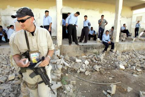 FALLUJAH, Iraq: An International Police Liaison Officer (IPLO) hired by US security company DYNCORP to help build the Iraqi police force walks among the rubble of a police station in the city of Fallujah, October 2005.