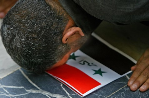 Baghdad, IRAQ: An Iraqi Shiite worshipper uses the Iraqi flag as a praying carpet as he performs Friday noon prayer at Imam Mussa al-Kazem shrine in Baghdad, 24 March 2006.