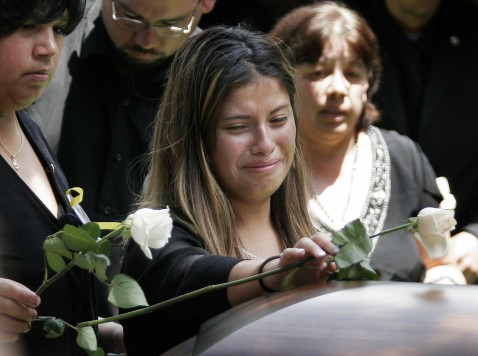 BROWNSVILLE, TX - JUNE 28: Christina Menchaca, 18, lays flowers on teh casket of her husband, 23-year-old Pfc. Kristian Menchaca, during his funeral June 28, 2006 in Brownsville, Texas.