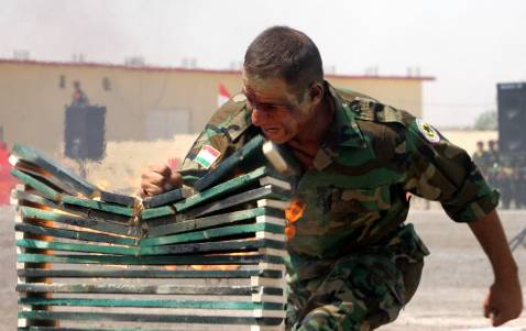 A Kurdish Peshmerga soldier crushes stacked bricks during a military ceremony 12 July 2006 held in the Kurdish regional capital of Arbil.