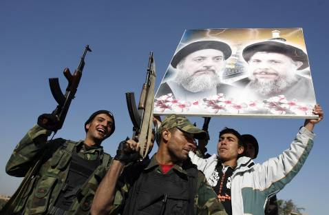 Baghdad, Dec. 30, 2006. Badr militiamen hold a picture of the late Mohammed Baqr Al-Sadr, father-in-law of Muqtada al-Sadr, and the late Mohammed Baqr Al-Hakim (L), brother of Abd al-Aziz al-Hakim after hearing the news Saddam Hussein's execution earlier