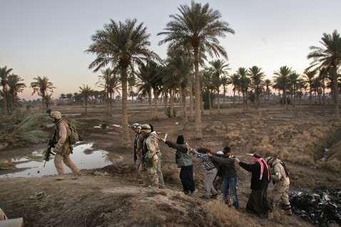 RAMADI-JANUARY 23, 2007: A U.S. Marine leads detainees towards a combat outpost. According to American forces, the detainees were captured after a someone in a vehicle opened fire on U.S. and Iraqi troops. The forces killed one and detained seven others from the vehicle and another following it.