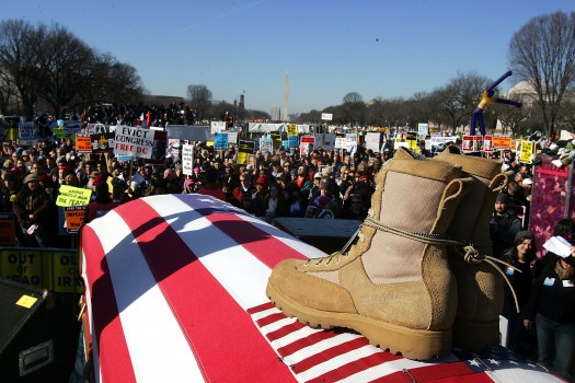 Soldier's boots and a symbolic flag-draped coffin at anti-war rally in Washington