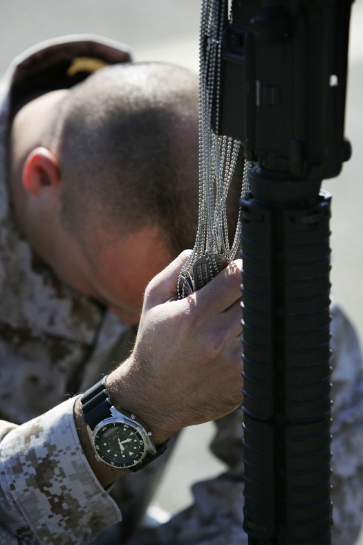 Lt. Corporal David Furness clutches the dog tags of fallen Marines he commanded in Iraq.