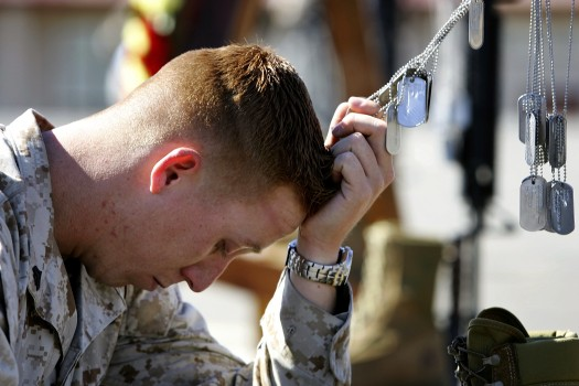 Corporal Brian Reimers, a combat correspondent attached to the 1st Battalion, 25th Marines, holds the dog tags of his fallen companions.