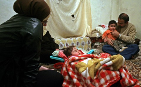 Beirut, LEBANON:  Iraqi refugee Sarah look at her sleeping daughter Rand as her husband plays with their son 21 March 2007 in a dark and damp room of an aparment in Beirut's Christian suburb of Dikwaneh.