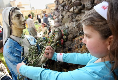Arbil, IRAQ: An Iraqi Christian girl puts flowers on a statue of the Virgin Mary as she celebrates Palm Sunday in the northern Kurdish city of Arbil, 01 April 2007.