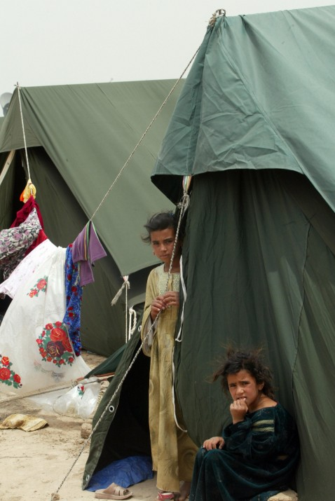 Young Iraqi refugees who fled the violence-striken Diyala province, northeast of Baghdad, stand by their tents, which were set up by Iraqi Red Cross workers in Baghdad's al-Husseiniya area on May 12, 2007