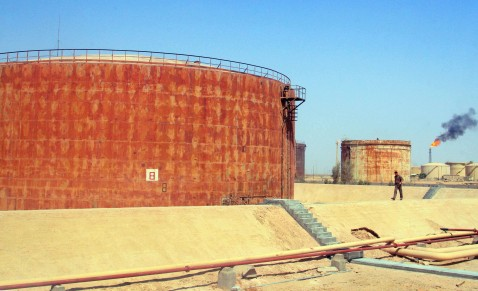 An Iraqi walks past oil reservoirs at the Iraqi Pipelines Company in Basra, June 2007.