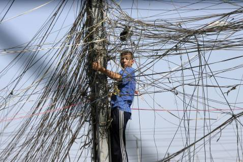 Baghdad, IRAQ: An Iraqi man bettles with a web of wires to try and reconnnect the electricity to his home in the Bayaa neighbourhood in southwest Baghdad, 07 June 2007.