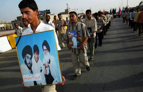 Supporters carry pictures of Muqtada al-Sadr and his father Muhammad, and of dead members of the Mahdi Army June 11, 2007 during a ceremony in the Sadr City to commemorate the fourth anniversary of the establishment of the Mahdi Army militia.