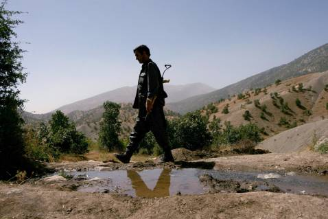 Baghdad, IRAQ: A Kurdish fighter patrols an area in the Iraqi part of Qandil Mountains near their headquarters on the Iraqi-Iranian-Turkish borders, 12 June 2007.