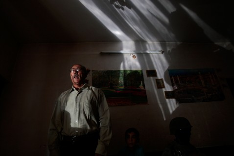 BAGHDAD, IRAQ - JUNE 18: A man suspected of being a terrorist bomb financier stands in his living room as troops enter his house June 18, 2007 in the tense Dora neighborhood of Baghdad, Iraq.