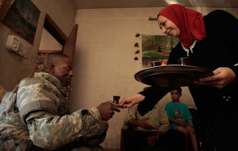 BAGHDAD, IRAQ - JUNE 18: An Iraqi woman of the household serves tea to 1st Sgt. Devin Winnegan of Smithfield, North Carolina.