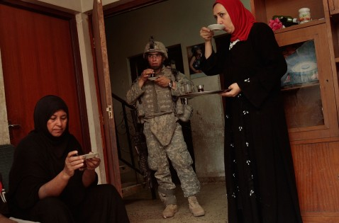 BAGHDAD, IRAQ - JUNE 18: Women sip tea and look on nervously as the man of the house, suspected of being a terrorist bomb financier, is questioned by U.S. troops.