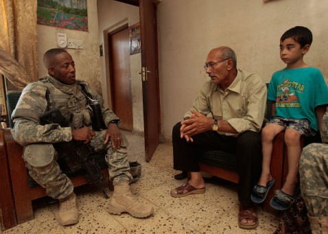 BAGHDAD, IRAQ - JUNE 18: First Sgt. Devin Winnegan of the 1st Squad, 4th Cavalry Regiment of the 1st Infantry Division talks to a man suspected of being a terrorist bomb financier as a boy in the household looks on.