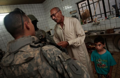 BAGHDAD, IRAQ - JUNE 18: A man suspected of being a terrorist bomb financier greets U.S. troops as they return to his house to arrest him June 18, 2007 in the tense Dora neighborhood of Baghdad, Iraq.