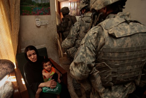 BAGHDAD, IRAQ - JUNE 18: A woman of the house holds a young boy as the man of the house is taken away on suspicion of being a terrorist bomb financier.