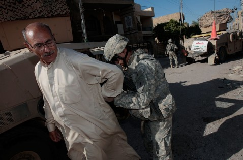 BAGHDAD, IRAQ - JUNE 18: A man suspected of being a terrorist bomb financier is handcuffed by Staff Sgt. Cesar Robles of Coachella, California June 18, 2007 in the tense Dora neighborhood of Baghdad, Iraq.