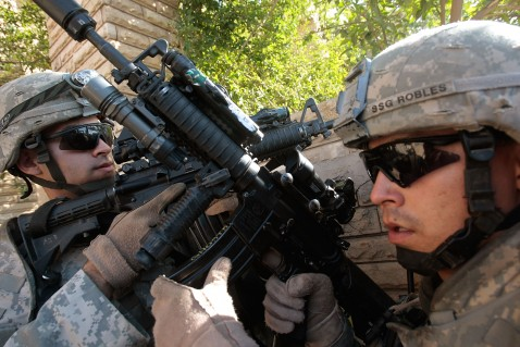 BAGHDAD, IRAQ - JUNE 18: Staff Sgt. Cesar Robles of Coachella, Calilfornia (R) and Lt. Alex Torres of Columbia, South Carolina (L) take positions while conducting house searches June 18, 2007 in the tense Dora neighborhood of Baghdad, Iraq.