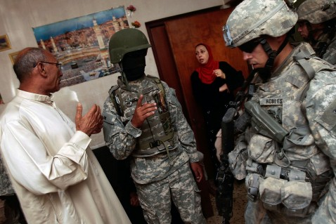 BAGHDAD, IRAQ - JUNE 18: A woman reacts as the man of the house is arrested on suspicion of being a terrorist bomb financier by U.S. troops June 18, 2007 in the tense Dora neighborhood of Baghdad, Iraq. The soldier in the mask is an Iraqi translator.