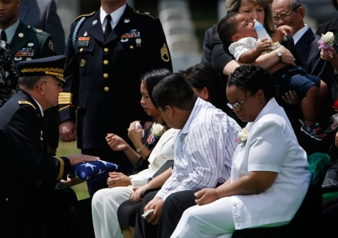 Eighteen-month-old Greg Sutton is carried away from his mother, Joane, while she accepts a U.S. flag from Brig. Gen. Thomas Seamands (L) that draped the casket of her husband Army Sgt. 1st Class Greg Lamonte Sutton.