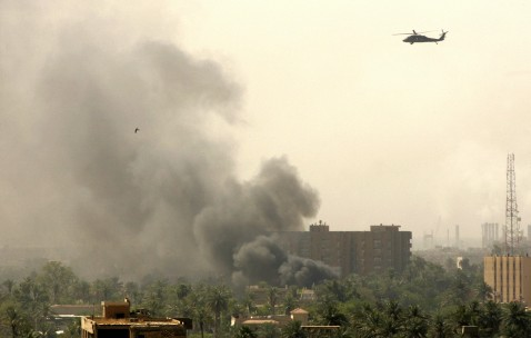 Baghdad, IRAQ: A US Blackhawk helicopter flies over thick smoke rising from the heavily fortified Green Zone in Baghdad, 21 June 2007.