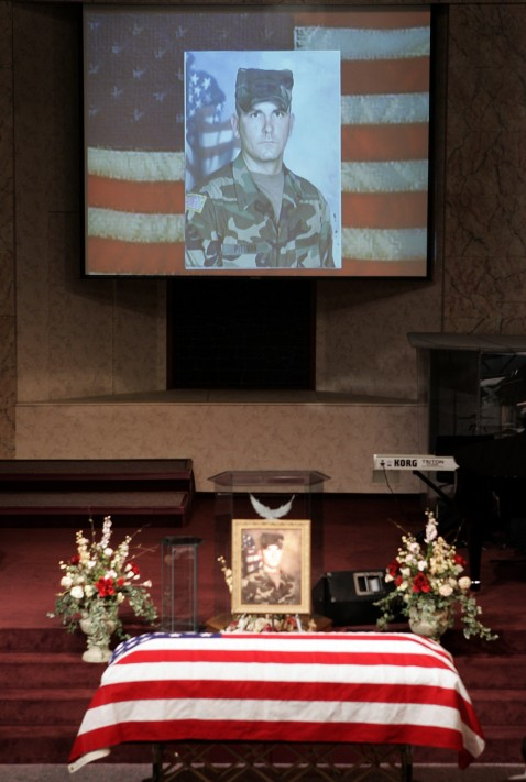 slideshow of family photos is shownabove the coffin of Pfc. Michael P. Pittman during his funeral services.