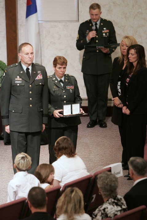 Military officials present a bronze star and purple heart to Jennifer Pittman during the funeral services.