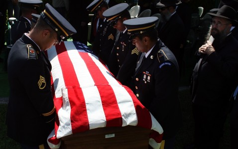 The flag drapped casket of U.S. Army Specialist Daniel Agami of the 1st Infantry Division is carried by a military honor guard as he is laid to rest.