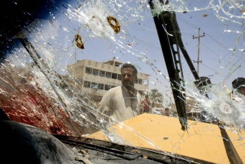 Baghdad, IRAQ: An Iraqi inspects the bullet-riddled windshield of a car at Baghdad's impoverished district of Sadr City, 27 June 2007.