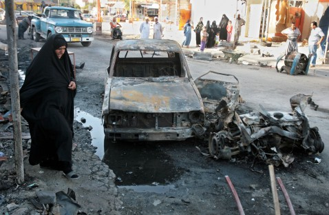 Baghdad, IRAQ: An Iraqi woman walks past the wreckage of a vehicle at the site of a car bomb blast that took place the day before in Baghdad 03 July 2007.