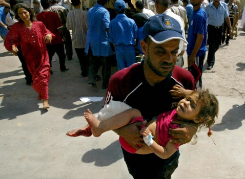 Kirkuk, IRAQ: An Iraqi rushes a wounded girl into a hospital in the oil rich city of Kirkuk, north of Baghdad, 07 July 2007.