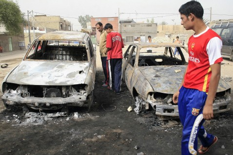 Baghdad, IRAQ: Iraqis inspect burnt cars at the site of an alleged overnight raid by US and Iraqi troops in Baghdad?s impoverished district of Sadr City, 10 July 2007. Residents said two people were killed and four wounded during the raid.