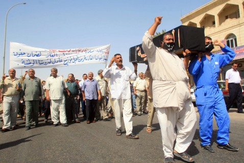 Basra, IRAQ: Iraqi oil workers shout slogans opposing the draft hydrocarbons bill at a protest organized by trade unions in the southern city of Basra, 16 July 2007.