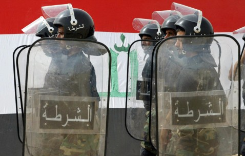 NAJAF, IRAQ: Iraqi police cadets parade against a background of the national flag during their graduation ceremony at Imam Ali Police Academy in the Iraqi central Shiite holy city of Najaf, 19 July 2007.