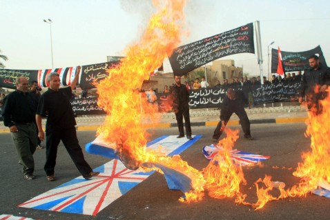 Basra, IRAQ: Iraqis torch the national flags of the United States, Israel, and Britain during a parade in the southern city of Basra, 19 July 2007.