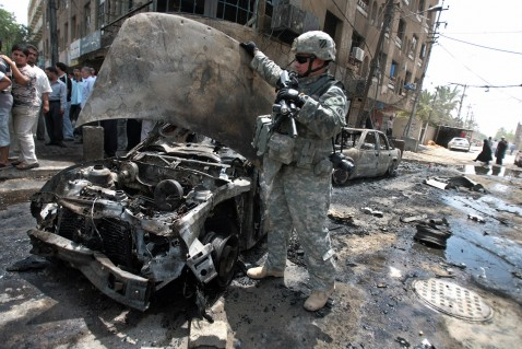 Baghdad, IRAQ: A US soldier inspects the wreckage of a car at the site where a car bomb exploded in central Baghdad's Karrada neighbourhood, 23 July 2007.