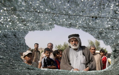 Baghdad, IRAQ: Iraqis inspect the shattered glass of a car hit during an alleged overnight US and Iraqi military raid at Baghdad's impoverished district of Sadr City, 25 July 2007. At least three people were killed and six others wounded during the raid.