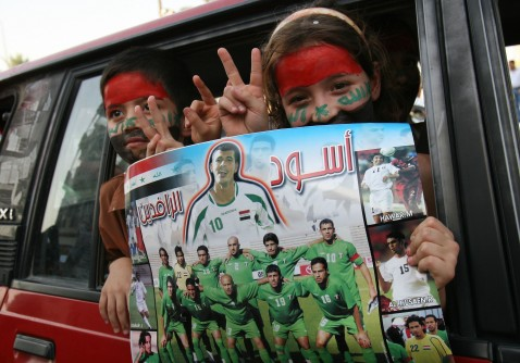 Baghdad - July 25: Iraqi children hold a poster of the Iraq National soccer team after their team beat South Korea during the 2007 AFC Asian Cup semifinal soccer match. Iraq faces off with Saudi Arabia in the Asian Cup finals Sunday in Jakarta.