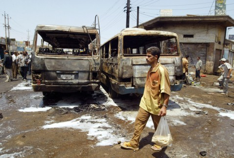 An Iraqi man carrying a bag of traditional Iraqi bread walks past burnt vehicles at the site of an explosion in central Baghdad 30 July 2007. The target appeared to be a microbus stop near Tayran Square, a bustling transport hub in the centre of the city